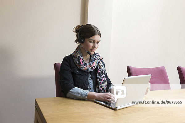 Woman wearing headset working on laptop