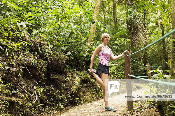 Woman in forest  stretching leg