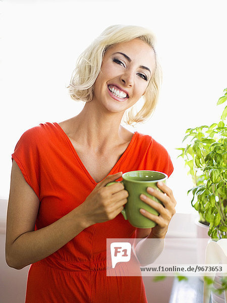Woman in red dress holding green mug