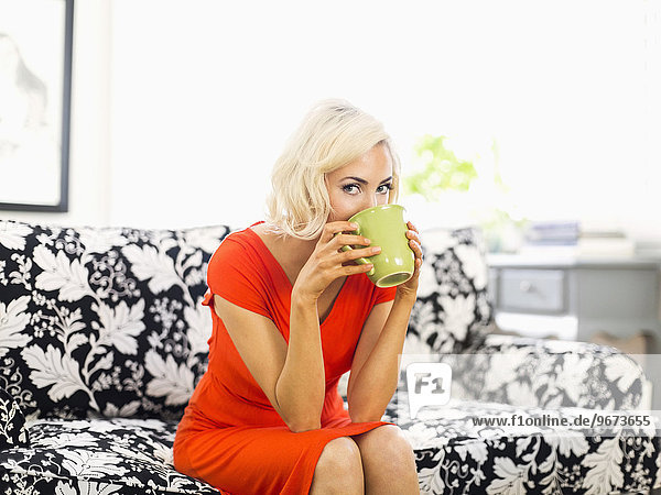 Woman in red dress sitting on sofa and drinking coffee
