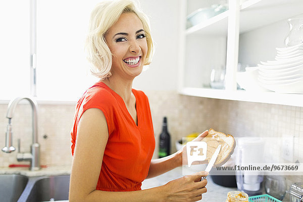 Woman making toast with peanut butter in kitchen and smiling to camera