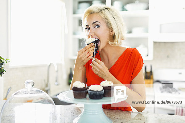 Woman eating muffins at kitchen