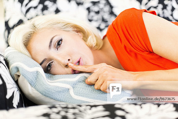 Close-up of woman lying down on sofa and keeping finger on lips