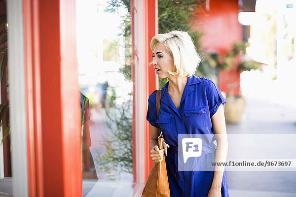 Woman in blue dress looking at window display