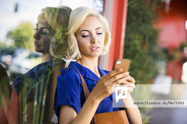 Woman leaning against window and using phone