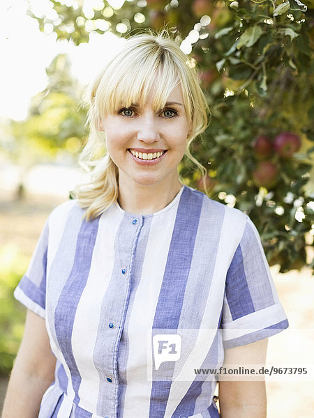 Portrait blond Frau Obstgarten