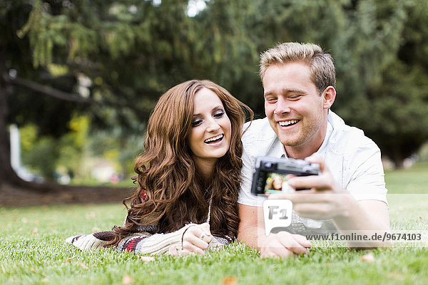 Portrait of young couple taking selfie in park