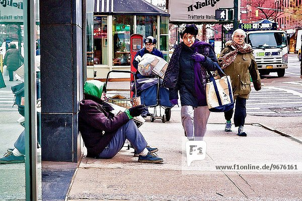 Elderly man holding a cup in his hand  begging for money. Two older women passing by. New York City.