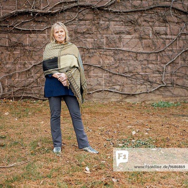 stehend Senior Senioren Efeu Hedera helix Frau bedecken Wand Beton