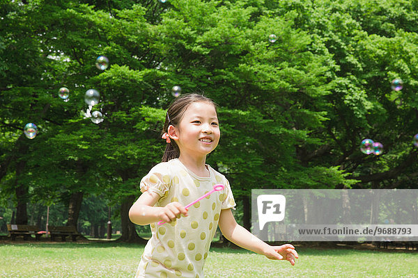 Japanese kid playing with soap bubbles in a park