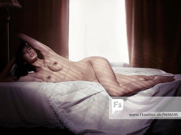 liegend liegen liegt liegendes liegender liegende daliegen junge Frau junge Frauen Schönheit Fotografie Beleuchtung Licht Bett Kunst Dunkelheit nackt