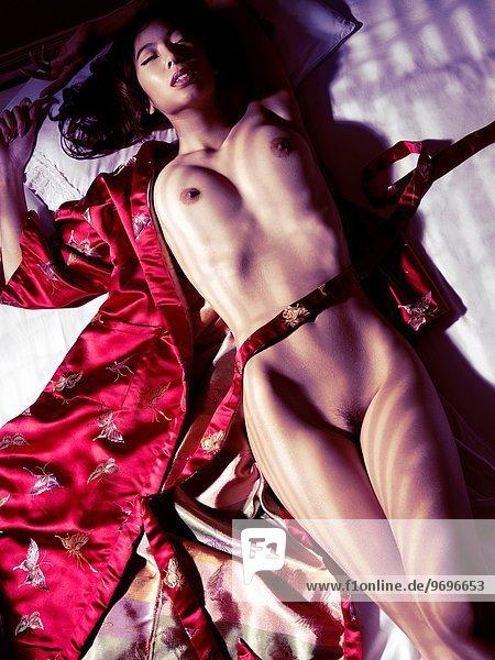 liegend liegen liegt liegendes liegender liegende daliegen Frau Schönheit Beleuchtung Licht Bett dramatisch rot nackt Dunkelheit Kimono