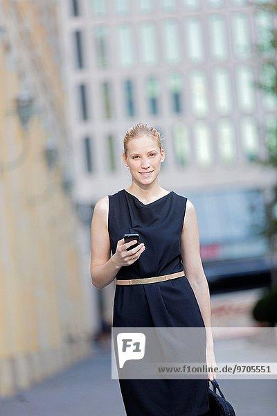 Handy Portrait Geschäftsfrau sehen Blick in die Kamera Kurznachricht Innenstadt