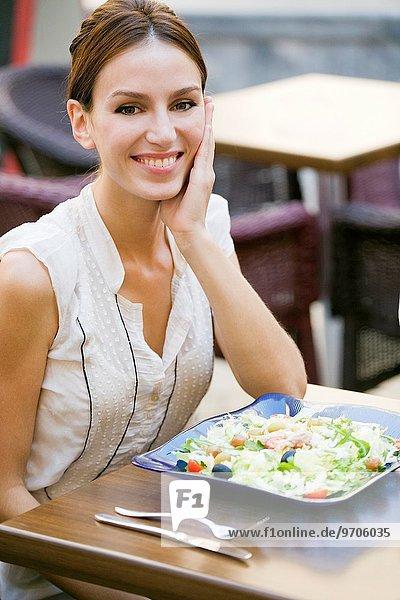 Außenaufnahme Frau Fröhlichkeit lächeln Salat Restaurant Blick in die Kamera freie Natur hübsch