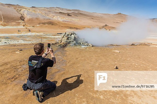 Photographer in geothermal field of mud pots  steam vents  and sulphur deposits at Hverarönd  Iceland.