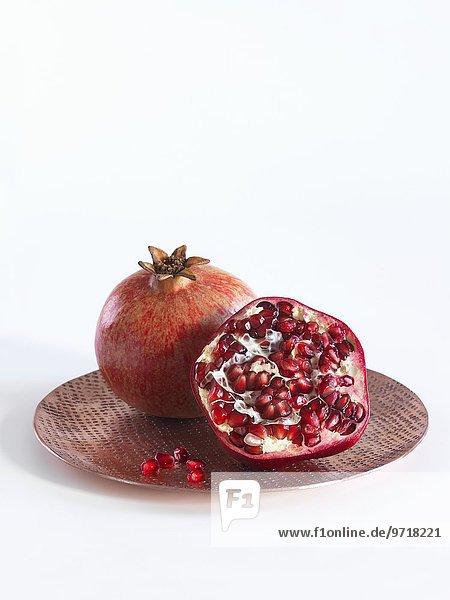 Ganzer und halber Granatapfel auf Kupferteller