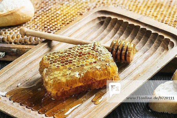 Honigwabe mit Honiglöffel in alter Holzschale