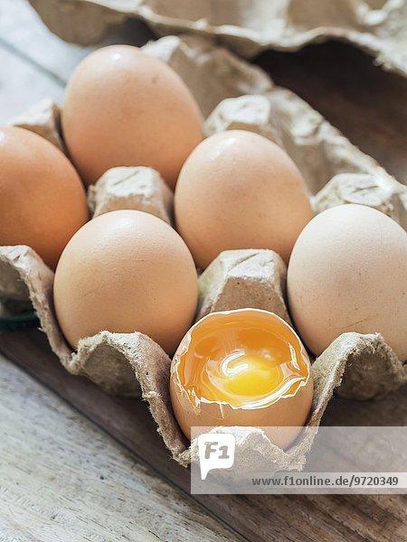 Sechs frische Bio-Eier im Eierkarton  eines aufgeschlagen