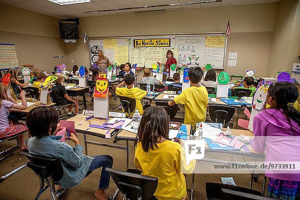 Multiracial students in an Irvine  CA  elementary school writing class are encouraged to create cutout artwork monsters to use as subject themes. Note sign in background.