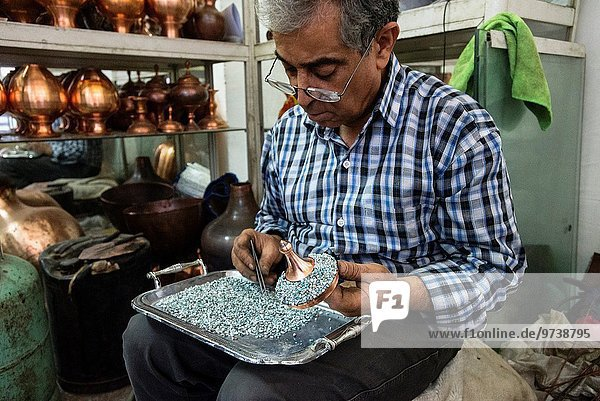 Artist sets mina stones for minakari  unique art of Esfahan  which means decorating metals with colorful and baked coats  Esfahan  Iran.