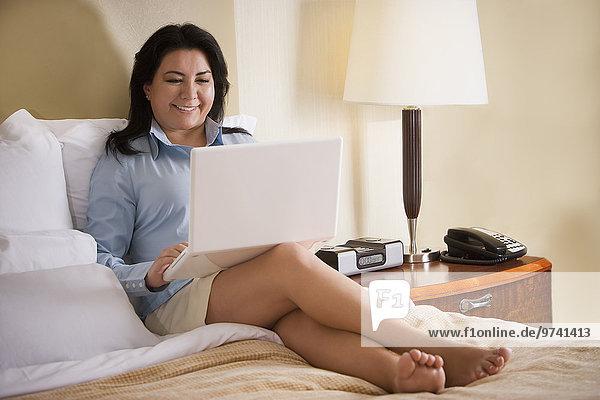 sitzend benutzen Geschäftsfrau Notebook Bett Chillipulver Chilli