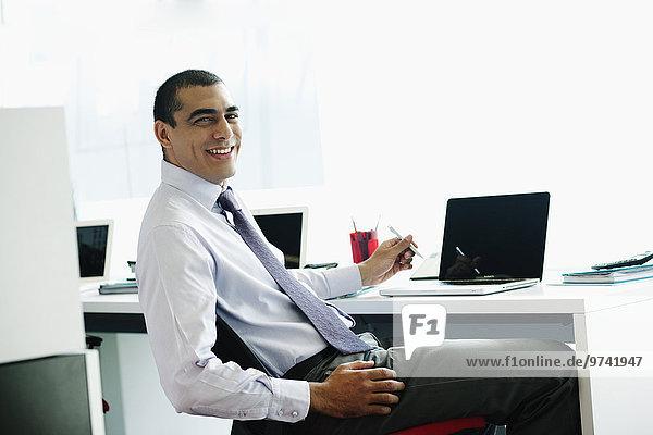 sitzend Schreibtisch Geschäftsmann lächeln