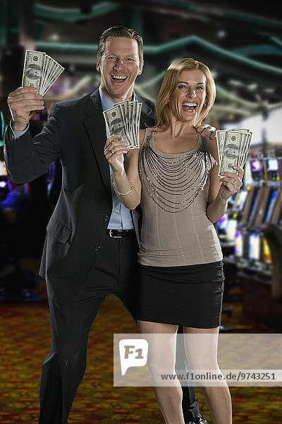 Excited Caucasian couple holding cash winnings in casino