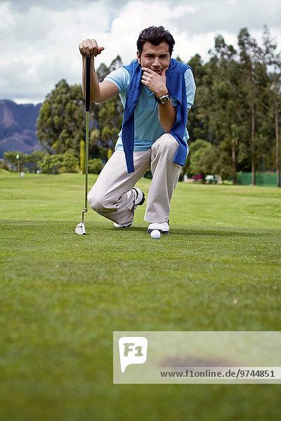 Hispanic man assessing golf course