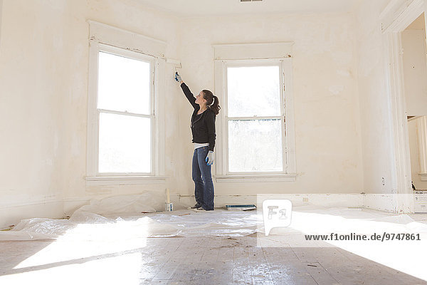 Mixed race woman painting walls of new home