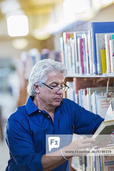 Older Hispanic man reading book in library