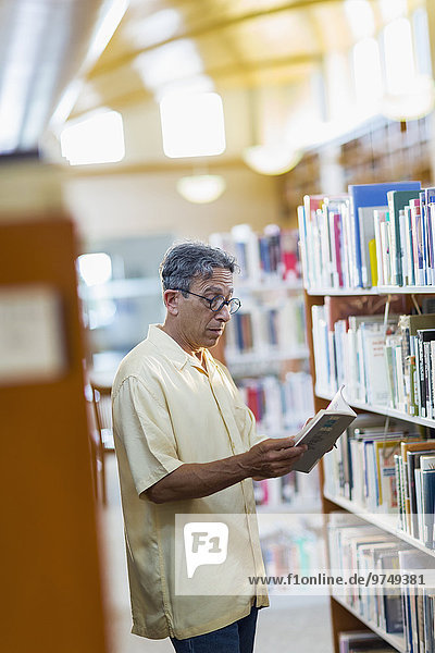 Older Caucasian man reading book in library