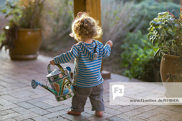 Caucasian baby carrying watering can