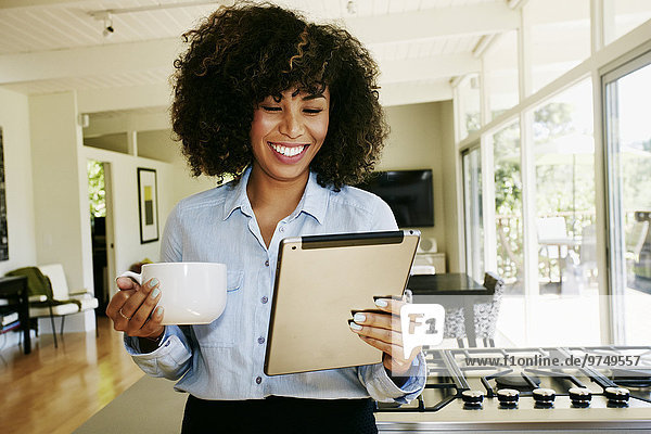 Mixed race businesswoman using digital tablet in domestic kitchen