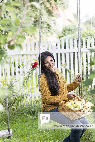 junge Frau junge Frauen schaukeln schaukelnd schaukelt schwingen schwingt schwingend Garten Schaukel