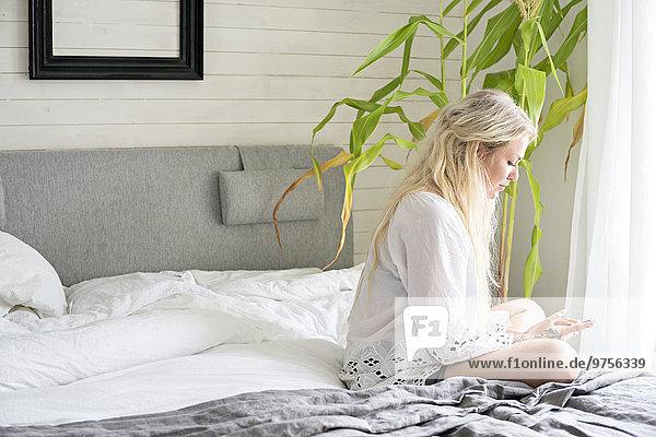 sitzend junge Frau junge Frauen Bett