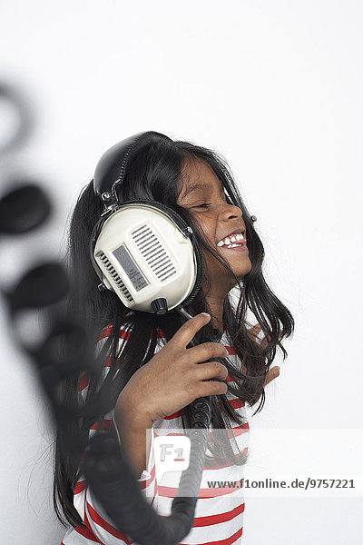 Smiling girl hearing music with headphones