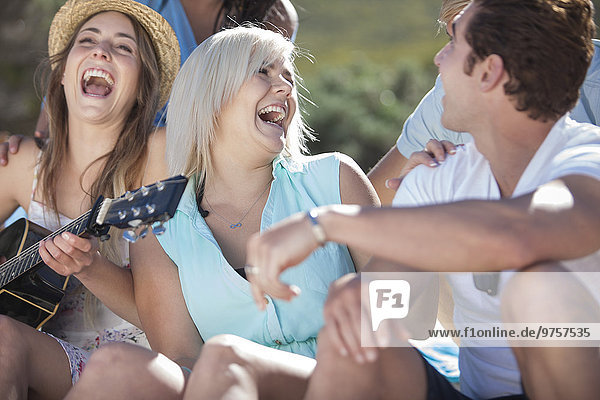 Friends with guitar having fun outdoors
