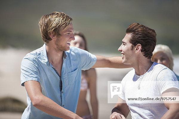 Zwei Freunde Arm in Arm am Strand