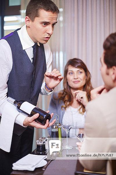 Kellner zeigt Geschäftspartnern Weinflasche im Hotelrestaurant