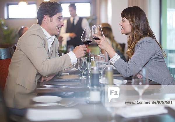 Couple clinking wine glasses in restaurant