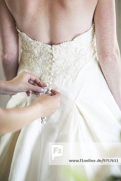 Brautjungfer  die das Brautkleid zuknöpft.