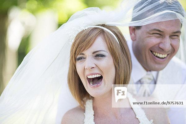 Lachender Bräutigam und Braut mit Schleier bedeckt  bereit für ihre Hochzeit.