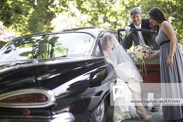 Braut  die vor ihrer Hochzeit mit Fahrer und Trauzeugin aus dem Auto steigt