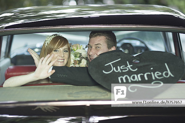 Glückliche Braut und Bräutigam winken im Auto nach der Hochzeit