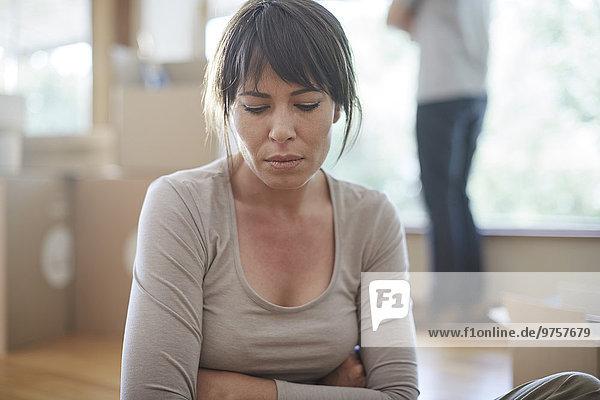 Frau sitzend und unglücklich beim Umzug