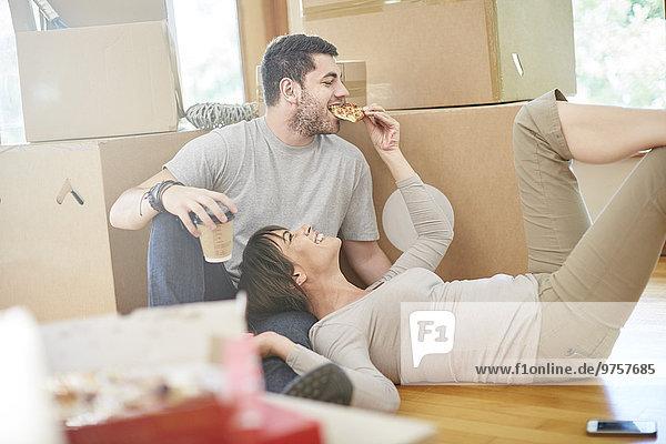 Ein Paar zieht um und isst Pizza.