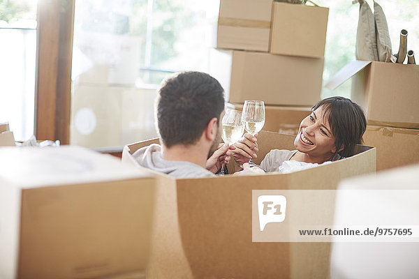 Paar Umzug in einer Kiste sitzend und klirrende Weingläser