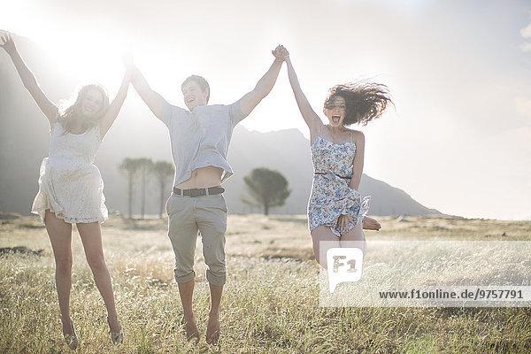 Südafrika  Freunde springen vor Freude im Feld