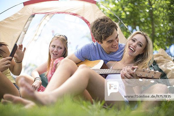 Glückliche Freunde  die im Zelt sitzen und Gitarre spielen.