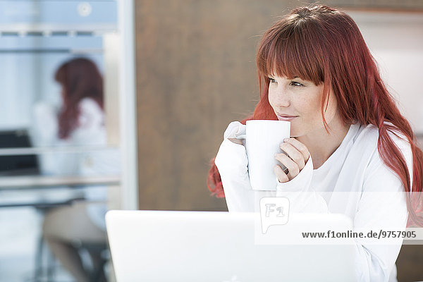 Young woman with laptop and cup of coffee in kitchen